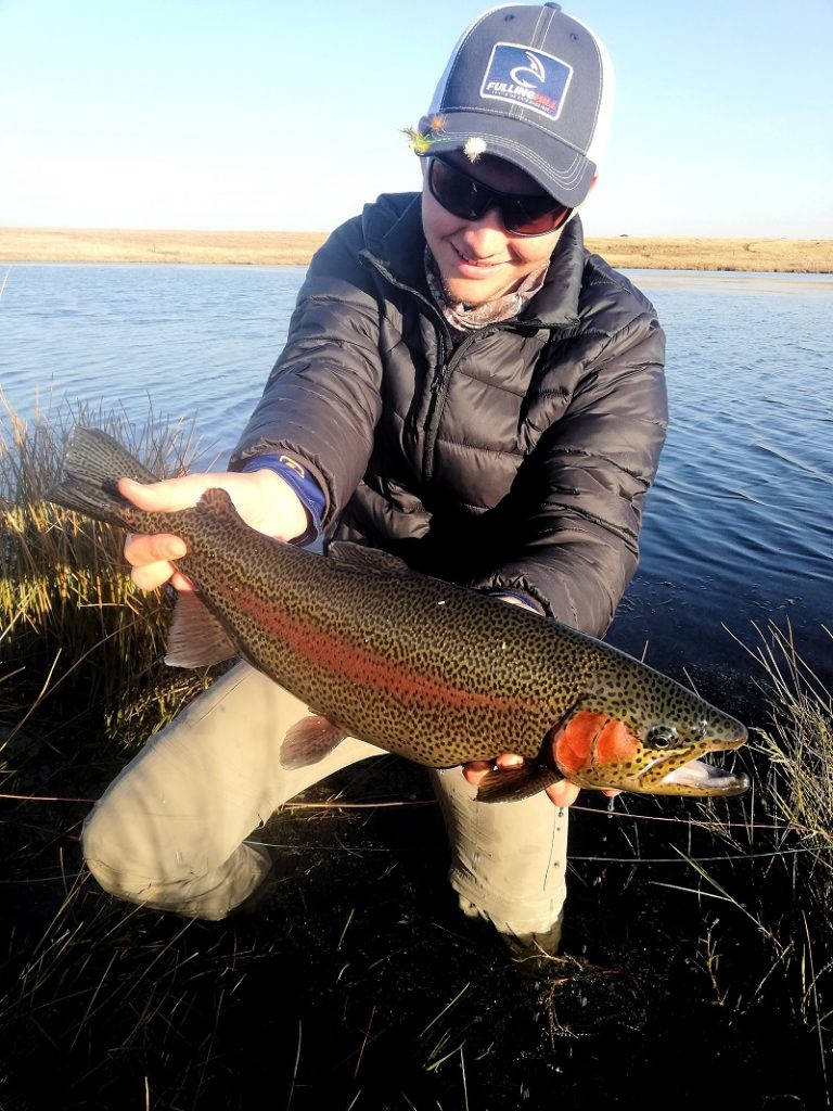 angler holding a rainbow trout caught in Dullstroom
